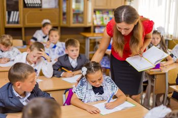Elementary School Classroom Children Students Teacher Helping Girl